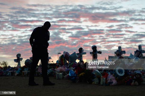 An Aurora Colorado Police officer visits the roadside memorial set up for victims of the theaters shooting massacre across the street from Century 16...