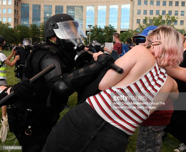 An Aurora police officer clashes with a protester with a baton during the Elijah McClain protest at the Aurora Municipal Center June 27 2020 Elijah...