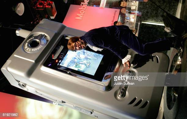 An Austin Powers impersonator hugs a giant LG cell phone at the 2005 Consumer Electronics Show January 6 2005 in Las Vegas Nevada The 15 million...