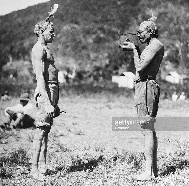 An Australian Aborigine man photographs a fellow member of his tribe on the Palm Islands off Northern Queensland