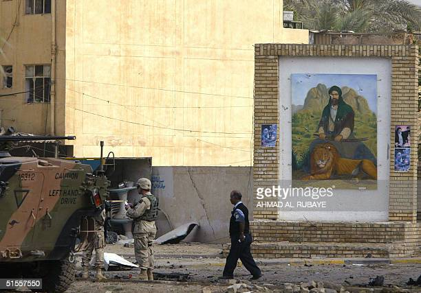 An Australian armoured vehicles secure the area following a blast close to a picture of Imam Ali 25 October 2004 in the Karrada district of Baghdad...