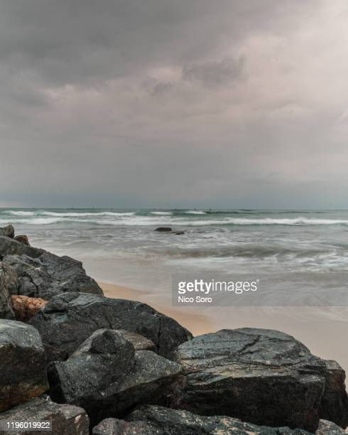 an australian beach during a cloudy summer day - moody sky stock pictures, royalty-free photos & images