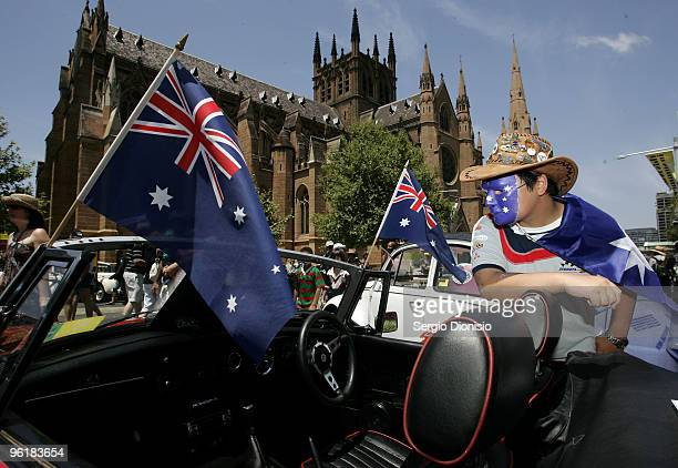 An Australian dressed in costume views a collection of vintage cars during the NRMA Motofest as Australia celebrates Australia Day at Hyde Park on...