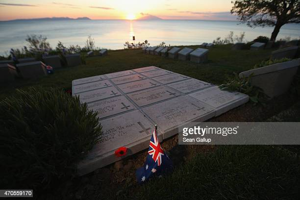An Australian flag and a commemorative poppy likely left by a visitor stand among the gravestones of Australian Anzac soldiers killed during the...