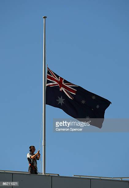 An Australian flag on the roof of the Sydney Football Stadium is lowered to halfmast during a prematch ANZAC Day ceremony prior to the round seven...