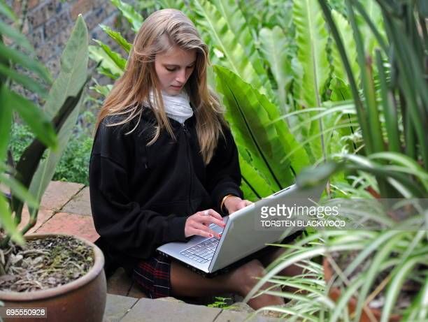 An Australian high school student uses 3G WiFi to connect her laptop to the internet while in a Sydney garden on June 16 2010 AFP PHOTO / Torsten...