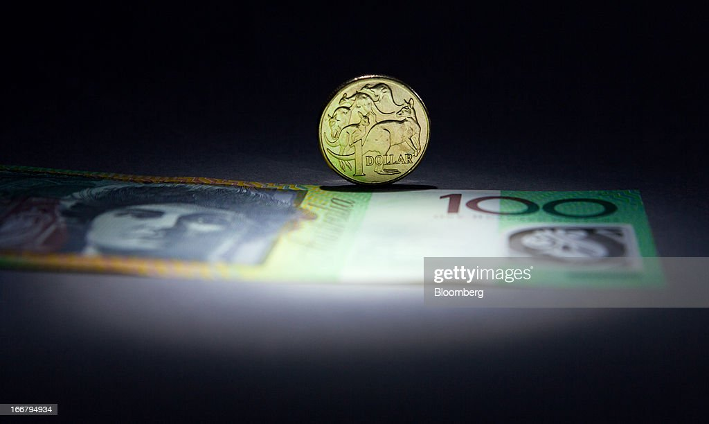 An Australian one-dollar coin and a one-hundred dollar banknote are arranged for a photograph in Sydney, Australia, on Wednesday, April 17, 2013. Direct trading between the Australian dollar and yuan started on April 10. Photographer: Ian Waldie/Bloomberg via Getty Images