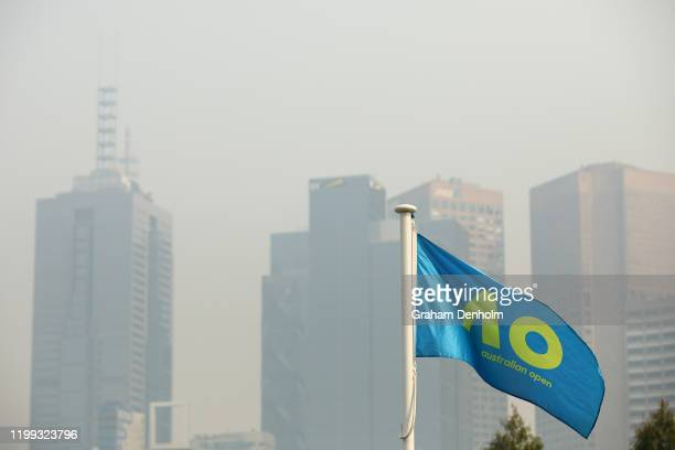 An Australian Open flag is seen with the city shrouded in smoke in the background ahead of the 2020 Australian Open at Melbourne Park on January 14...