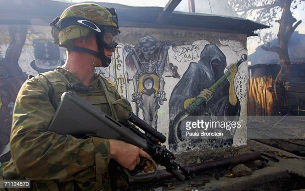 An Australian peacekeeping soldier stands guard while an entire block of homes burn on June 5 2006 in Dili East Timor Australia wants the United...