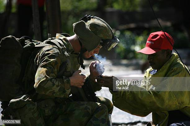 An Australian soldier and a Timorese firefighter share a cigarette after putting out another fire in East Timor's capital Dili Many buildings have...