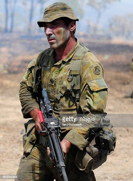 An Australian soldier from the 4th Field Artilery Regiment carries his Minimi machine gun during an Army fire power demonstration at Range Control...