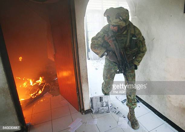 An Australian soldier helps to put out a fire in the East Timorese capital Dili Street fighting between rival gang continues and many of the city's...