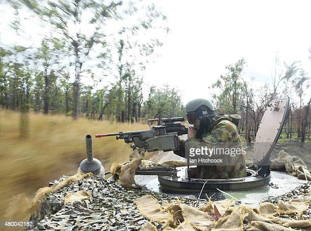 An Australian soldier operates a machine gun on the top turret of a Bushmater amoured vehical as part of exercise Talisman Sabre on July 9 2015 in...