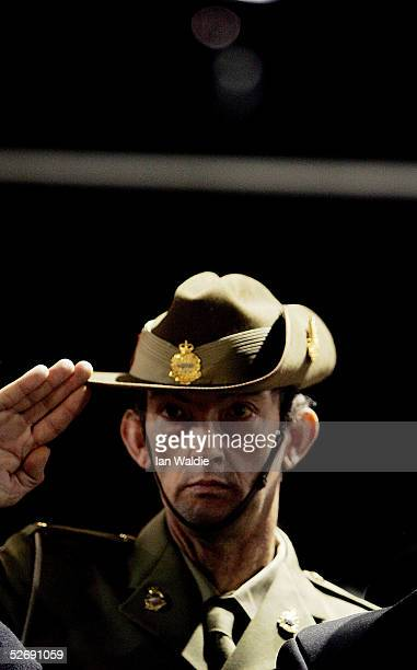 An Australian soldier salutes during a dawn service for Anzac Day April 25 2005 in Sydney Australia Australians and New Zealanders are today...