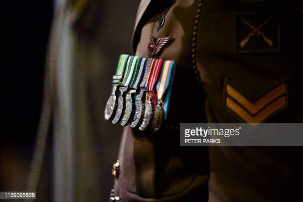 An Australian soldier stands at attention as his medals are illuminated during the Anzac Day dawn service at the Cenotaph in Sydney on April 25 2019...