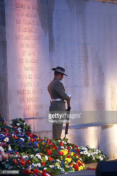 An Australian soldier stands in front of a wall bearing the WWI dead soldiers' names as he attends a dawn service at the Australian War Memorial on...