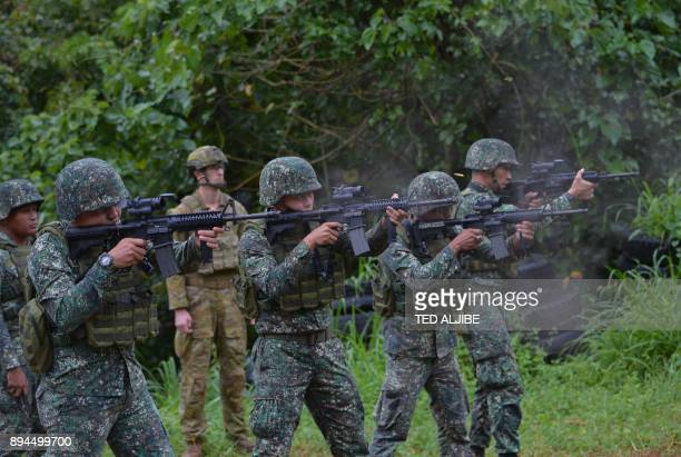An Australian soldier supervises as Philippine Marines fire their weapons during a demonstration at Military Operation Urbanized Terrain training...