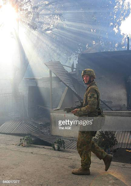 An Australian soldier walks past burnt out buildings in East Timor's capital Dili Street fighting between rival gangs continues in the city resulting...