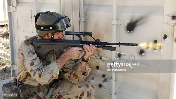 An Australian soldier who is role playing as an enemy soldier fires his rifle as US Marines from the 31st Marine Expeditionary Unit attack during the...