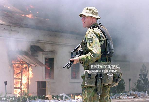 An Australian soldiers keeps his weapon at the ready in front of a blazing building 29 September 1999 after the fire set by unknown arsonists erupted...