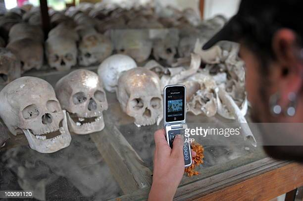 An Australian tourist takes picture of skulls displayed at the Choeung Ek killing fields memorial near Phnom Penh on July 26 2010 A former Khmer...