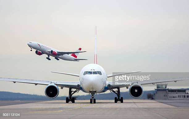 An Austrian Airlines AG passenger aircraft taxis along the tarmac as an aircraft takes off beyond at Vienna International Airport, operated by...