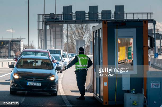 An Austrian border policeman gestures at the AustroHungarian border in Nickelsdorf Austria near Hegyeshalom Hungary on March 22020 Austria will post...