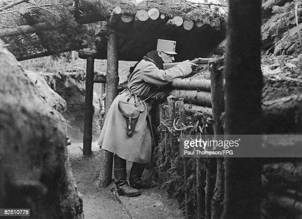 An Austrian soldier aims through a loophole in one of the outpost Carpathian trenches during World War I circa 1915