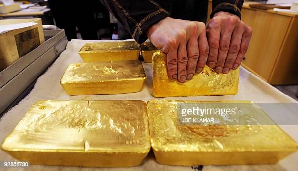 An Austrian worker handles ten kilogram 'raw' gold bars in Austrian gold bullion factory Oegussa in Vienna on October 8 2008 Oegussa announced on...