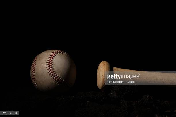 An authentic Rawlings used baseball from the 2012 Major League Baseball season showing the red stitching and markings next to a bat handle 16th May...