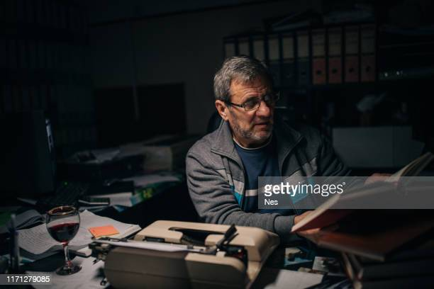 an author writing his novel on a typewriter - authors foto e immagini stock