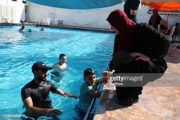 An autistic Palestinian boy swims in a pool as his mother interacts with him during a rehabilitation summer camp in the northern Gaza Strip August...