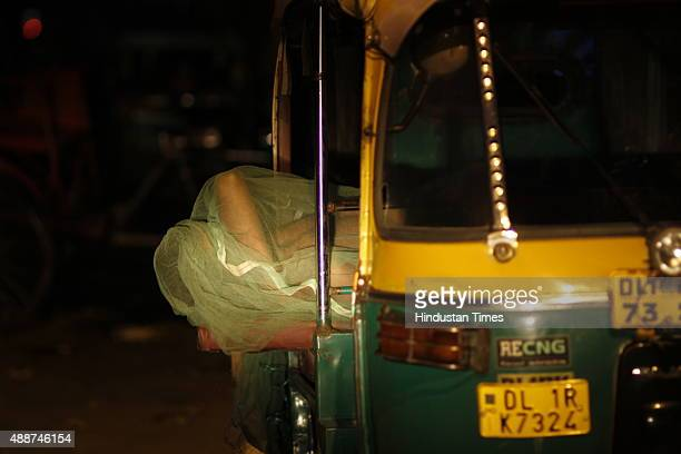 An auto driver sleeps while covering himself under mosquito net amid dengue outbreak on September 17 2015 in New Delhi India Delhi remained in the...