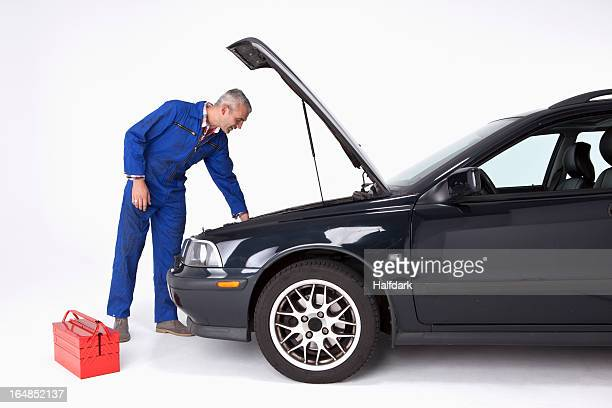 An auto mechanic looking under the hood of a car