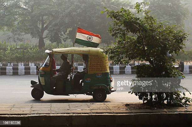 An auto rickshaw carrying the Indian national flag drives on a highway during a hazy day in New Delhi on November 12 2012 The Diwali festivities on...