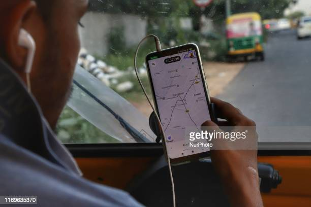 An auto rickshaw driver checks Google map while waiting for the passengers in New Delhi India on 18 September 2019