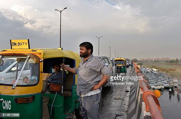 An auto rickshaw driver waits as he was stuck in huge traffic Jam due to the Art of Living foundation's 3daylong World Culture Festival Near...