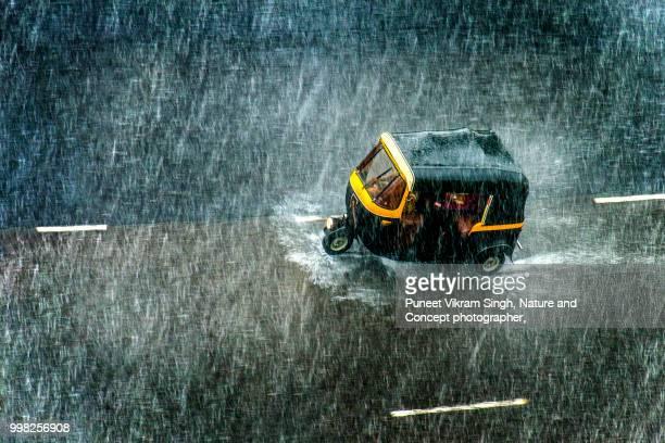 an auto rickshaw on the mumbai road during a heavy rainfall - rainy season stock pictures, royalty-free photos & images