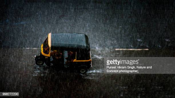 an auto rickshaw on the mumbai road during a heavy rainfall - monsoon stock pictures, royalty-free photos & images