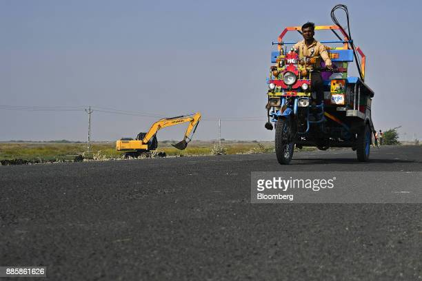 An auto rickshaw travels along a road past a Hyundai Construction Equipment Inc excavator operating at an under construction sewerage system on the...