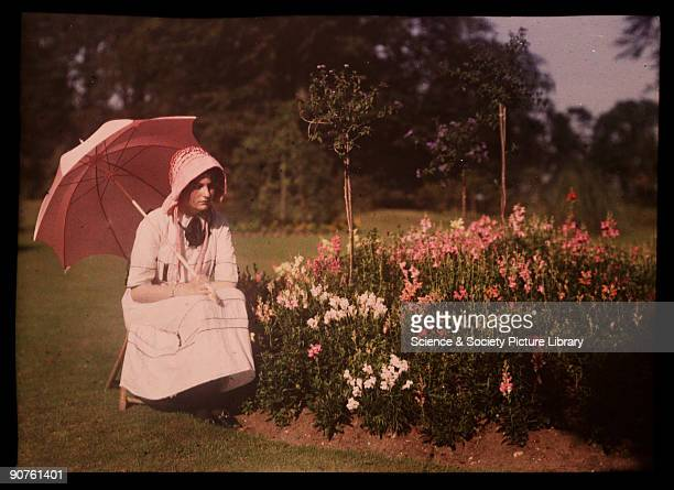 An autochrome of a girl daughter of the photographer with a parasol by a flower bed taken by Etheldreda Janet Laing In the summer of 1908 Laing took...