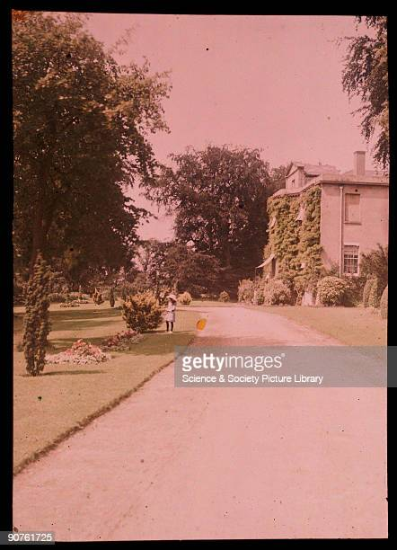 An autochrome of a large detached house and its garden and driveway taken by Etheldreda Janet Laing in about 1910 A little girl in a white bonnet...