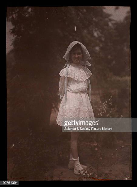 An autochrome of a smiling young girl daughter of the photographer wearing a bonnet and lace dress standing in a garden taken by Etheldreda Janet...