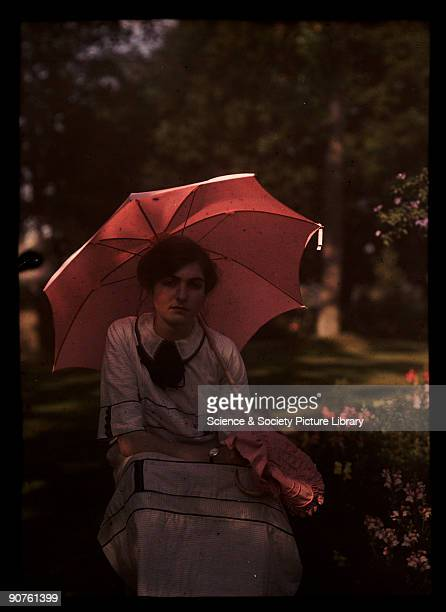 An autochrome of a young girl daughter of the photographer sitting in the shade in a garden holding a parasol over her shoulder taken by Etheldreda...