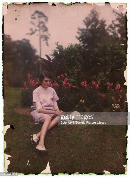 An autochrome of a young girl in a garden next to a flowerbed taken by Etheldreda Janet Laing in about 1910 The young girl her straw bonnet on the...