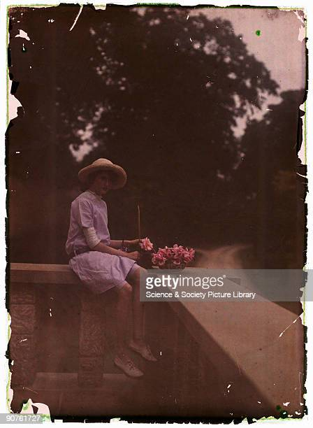 An autochrome of a young girl sitting on a balcony next to a bowl of flowers taken by Etheldreda Janet Laing in about 1910 The young girl her faced...