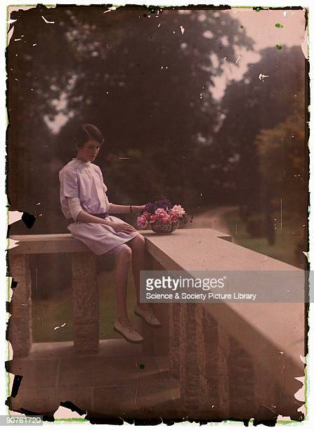 An autochrome of a young girl sitting on a balcony with a bowl of flowers taken by Etheldreda Janet Laing in about 1910 The young girl is probably...