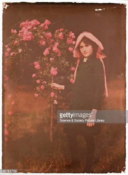 An autochrome of a young girl standing in a garden next to some rambling roses taken by Etheldreda Janet Laing in about 1910 As a young woman Laing...