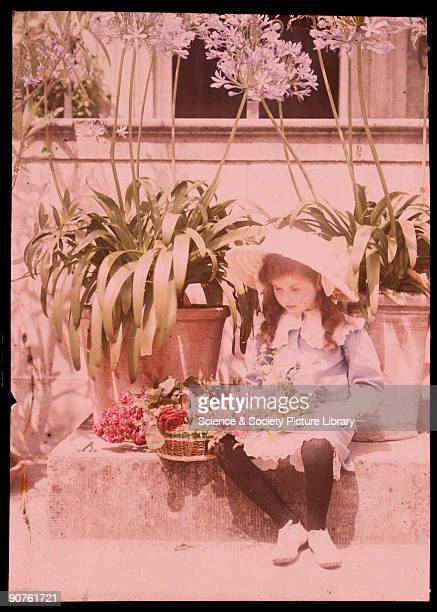 An autochrome of a young girl surrounded by flowers and potted plants taken by Etheldreda Janet Laing in about 1910 This little girl happily sits on...