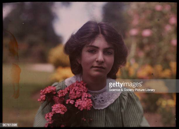 An autochrome of her daughter in a garden holding a brightly coloured bunch of pink flowers taken by Etheldreda Janet Laing In the summer of 1908...